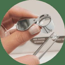 lady hand using jewelry loupe view round diamond tweezers up close