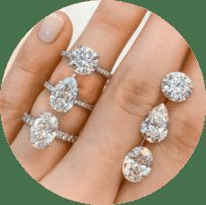 three diamond engagement rings and loose diamond shapes worn on ladies hand
