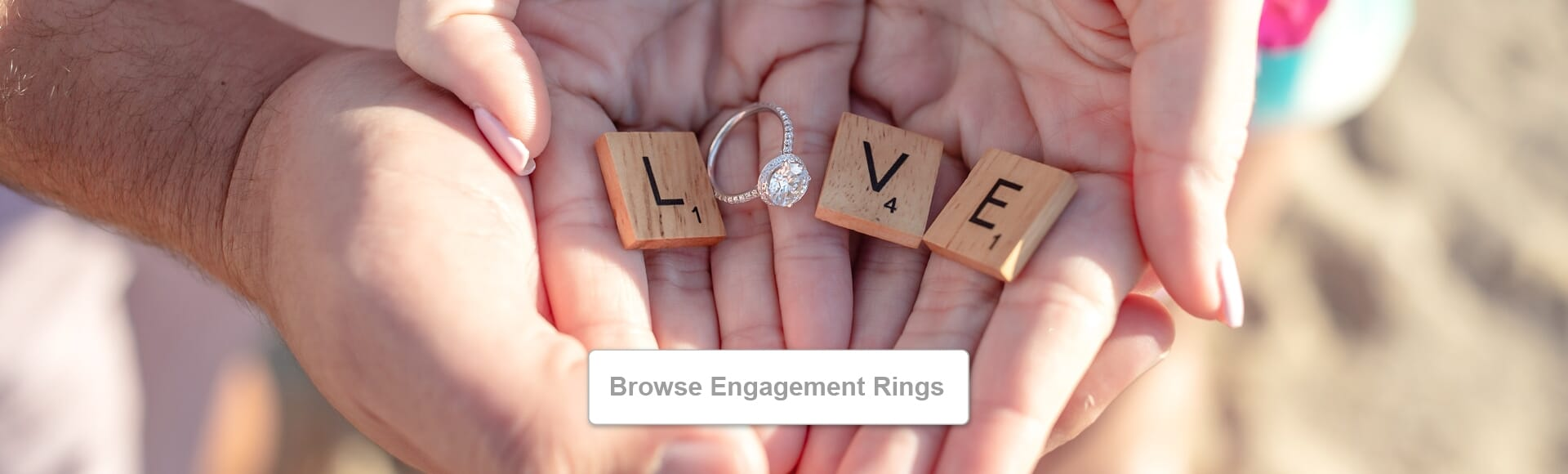 Hands hold engagement ring and scrabble pieces