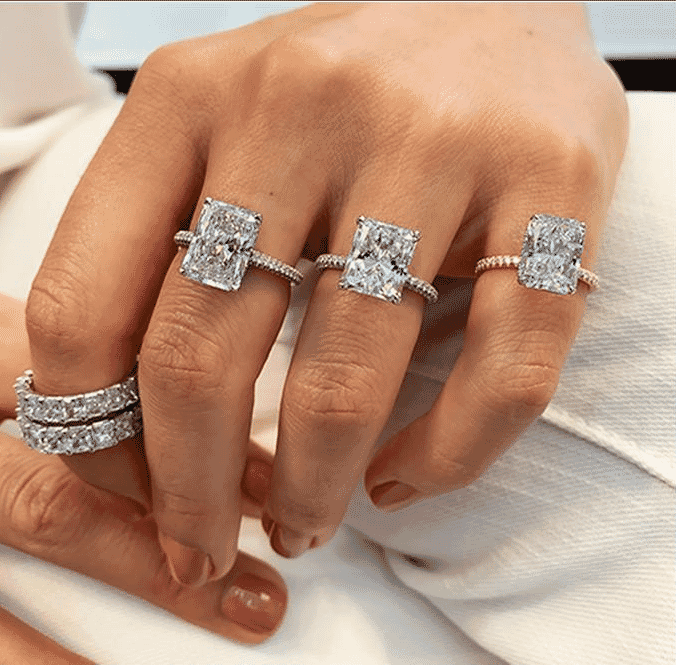 ladies hand wearing three radiant cut engagement rings and diamond eternity bands