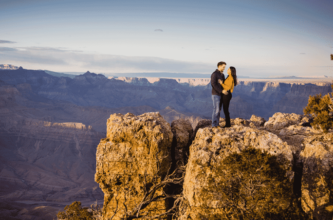 engagement proposal couple standing on mountain edge